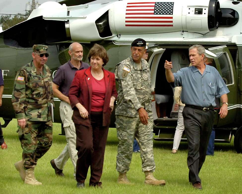 FILE- In this Sept. 5, 2005 file photo. President Bush, right, accompanied by Louisiana Gov. Kathleen Blanco, arrives in Baton Rouge, La., for a briefing at the state Office of Emergency Preparedness, following the devastation caused by Hurricane Katrina. Shown with the president are, from right, Army Lt. Gen. Russel Honore, Homeland Security Secretary Michael Chertoff, and Maj. Gen. Bennett Landreneau, head of the Louisiana National Guard. Blanco, who became Louisiana's first female elected governor only to see her political career derailed by the devastation of Hurricane Katrina, died Sunday, Aug. 18, 2019. She was 76. (Patrick Dennis/The Advocate via AP, Pool, File)