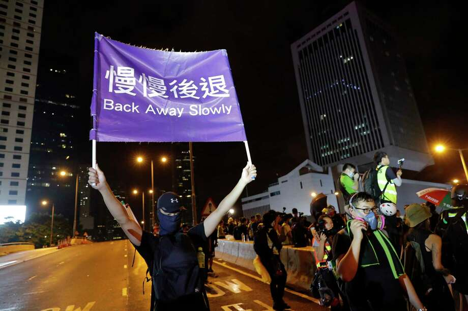 "A demonstrator holds up a sign reading ""Back away slowly"" to encourage other demonstrators to leave, near the Chinese Liaison Office in Hong Kong, Sunday, Aug. 18, 2019. Protesters turned Hong Kong streets into rivers of umbrellas Sunday as they marched through heavy rain from a packed park and filled a major road in the Chinese territory, where mass pro-democracy demonstrations have become a regular weekend activity this summer. (AP Photo/Vincent Thian) Photo: Vincent Thian / Copyright 2019 The Associated Press. All rights reserved"