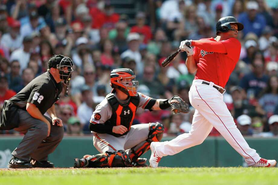 Boston Red Sox's Rafael Devers, right, follows through on an RBI double in front of Baltimore Orioles' Chance Sisco during the sixth inning of a baseball game in Boston, Sunday, Aug. 18, 2019. (AP Photo/Michael Dwyer) Photo: Michael Dwyer / Copyright 2019 The Associated Press. All rights reserved