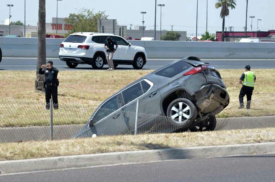 Oficiales de policía de Laredo fotografían e investigan un accidente de tres vehículos en el canal junto a la avenida San Darío, el domingo 18 de agosto de 2019. Photo: Christian Alejandro Ocampo /Laredo Morning Times / Laredo Morning Times