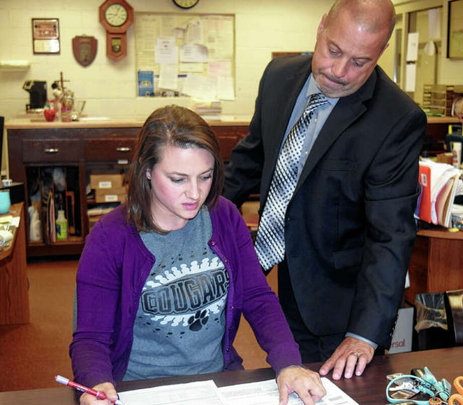 Superintendent Kevin Blankenship helps Winchester teacher Breann Nichols fill out paperwork Friday at the Winchester District Office.