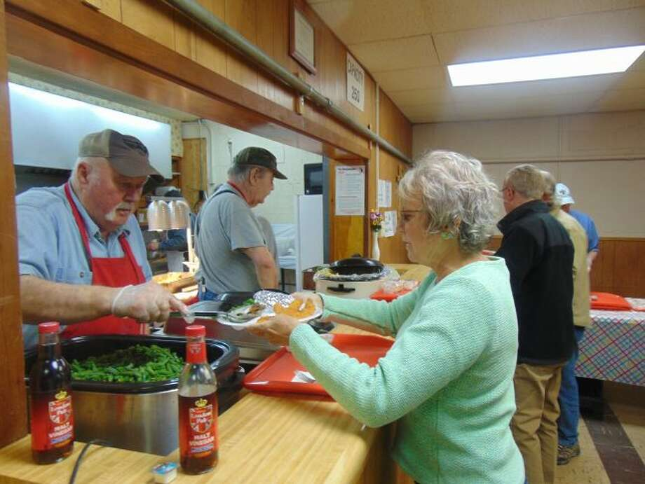 Members of St. Bernard Church serve up some fried fish and all the fixings to guests. (Star photo/Shanna Avery)