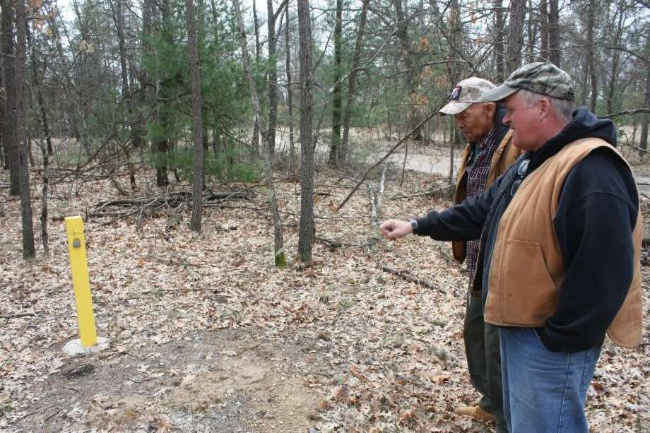 Pleasant Plains Trustee Clint Jackson, left, and zoning administrator Bob Sanders, right, point out one of the many testing wells on the polluted site. (Pioneer photo/Tim Rath)