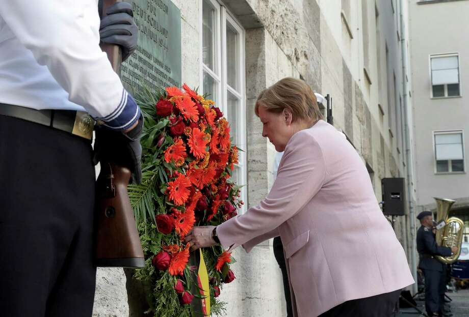 German Chancellor Angela Merkel adjusts a wreath during a memorial event at the Defence Ministry in Berlin, Germany, Saturday, July 20, 2019. On July 20, 2019 Germany marks the 75th anniversary of the failed attempt to kill Hitler in 1944. (AP Photo/Michael Sohn) Photo: Michael Sohn / Associated Press / Copyright 2019 The Associated Press. All rights reserved