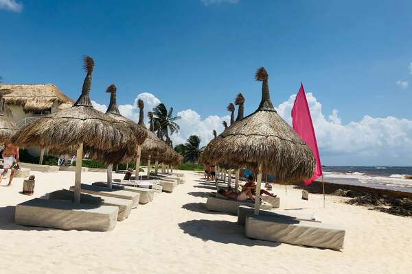 A few tourists are seen at the beach where Sargassum seaweed covers the shore near Tulum in Quintana Roo State, Mexico, on May 24, 2019. - Worried about the increase in the arrival of Sargassum at the Caribbean beaches, scientists, hotel owners and government officials are trying to find ways to get rid of it. Tons of this seaweed are upsetting tourists as locals work around the clock to remove them from the beaches. (Photo by Daniel SLIM / AFP) (Photo credit should read DANIEL SLIM/AFP/Getty Images)