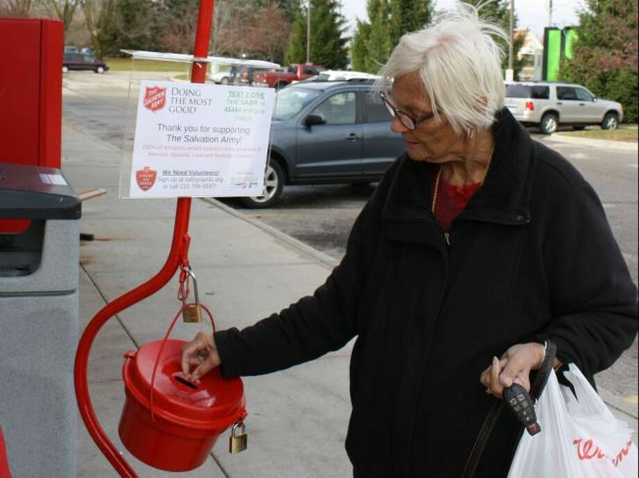 Jackie Roman makes a donation at a Salvation Army red kettle on Nov. 16, 2017, in Big Rapids. (Herald Review file photo)