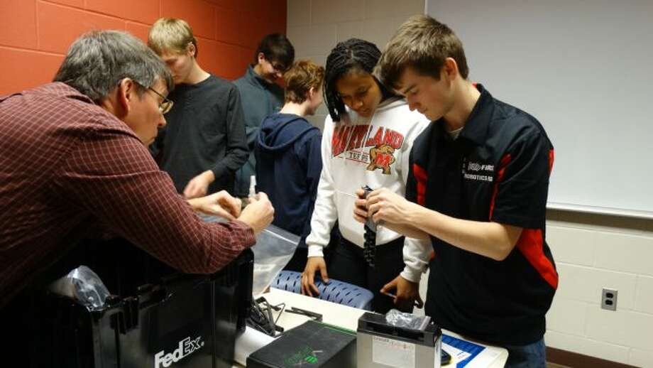 Members of the Big Rapids High School robotics team search through and note each of the pieces in the kit of parts they received during the FIRST Robotics kickoff event on Saturday at Ferris State University. (Herald Review photos/Meghan Gunther-Haas)