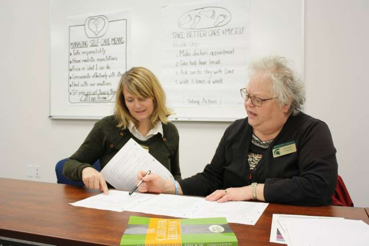 Pamela Daniels (left) and Shannon Lindquist, both educators with Michigan State University Extension, review the survey responses from a previous Powerful Tools for Caregivers workshop. MSUE will offer the workshop at no charge for six weeks beginning Jan. 26 in Evart. (Herald Review photo/Candy Allan)