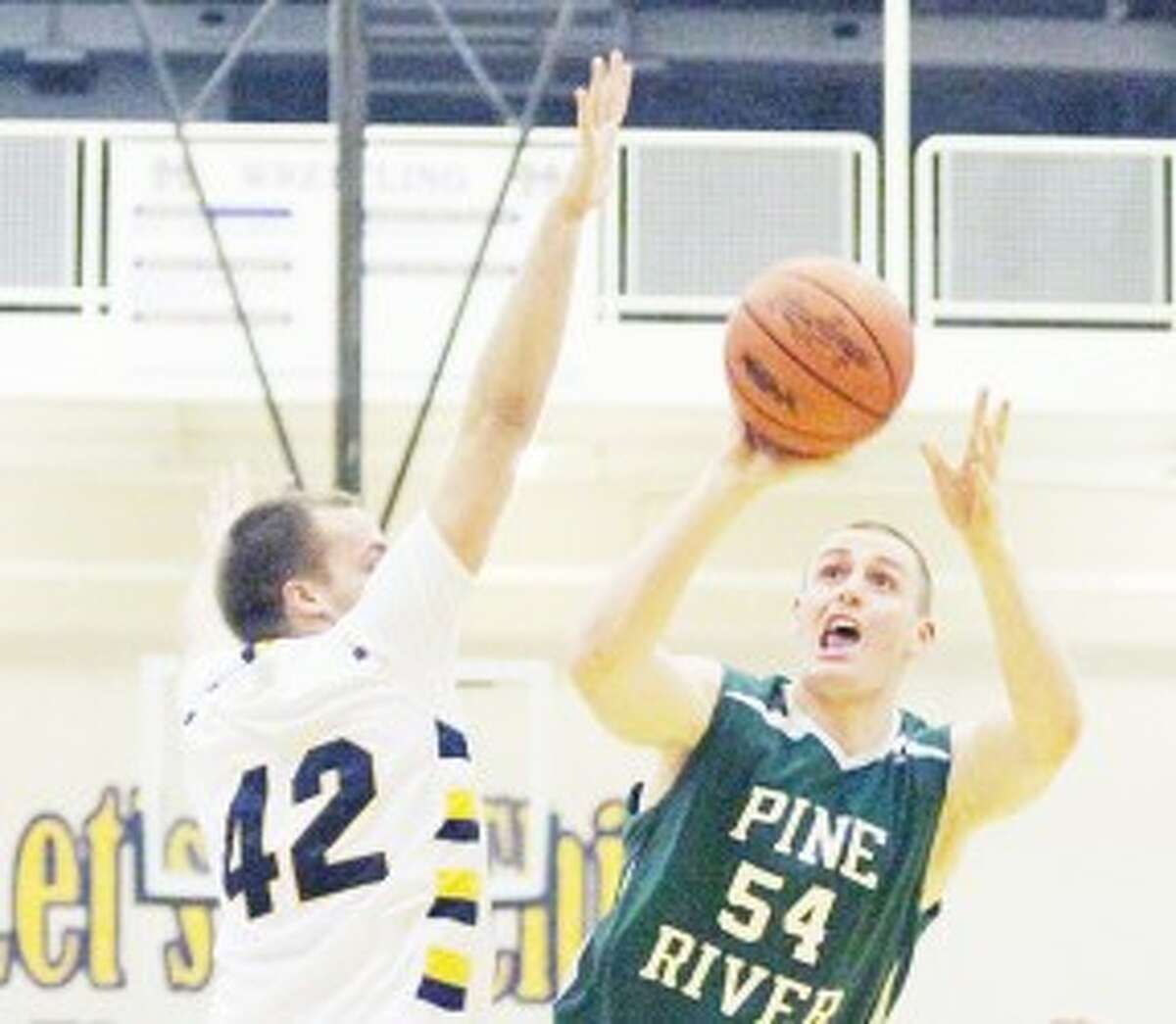 working for the win: Pine River's Lincoln Erickson (54) tries to get a shot off over Manistee's Jordan MacArthur during Monday's basketball contest. (Herald Review photo/Matt Wenzel)
