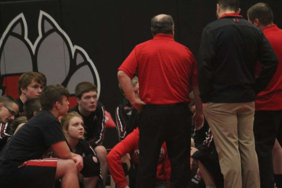 Reed City wrestlers talk with coach Roger Steig after a match.