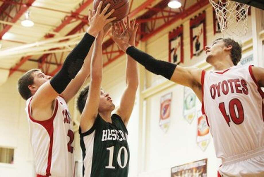 TEAM EFFORT: Reed City's Jake Vincent (right) and Ryan Willis (left) go up for a rebound on Monday against Hesperia. (Pioneer photo/Bob Allan)