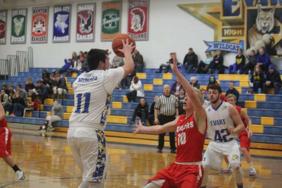 Evart's Cameron Martin (left) goes to the basket.