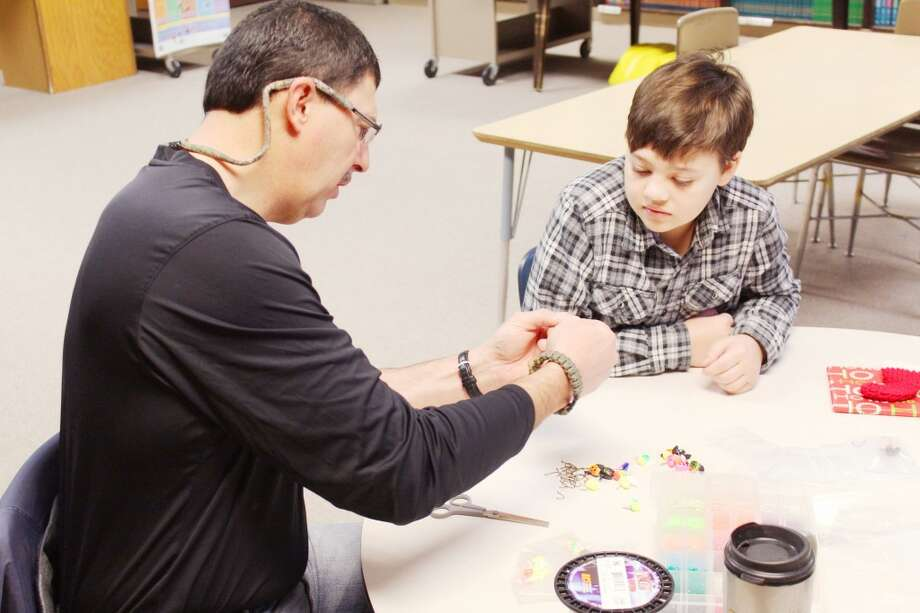 SPECIAL FRIENDS: Mark Romanack (left) and fifth grader Rees Beagle make lures to use in the spring. The pair were put together through the Brighten Up Tustin mentoring program that fosters relationships between students and their mentors and growth. (Herald Review photos/Sarah Neubecker)