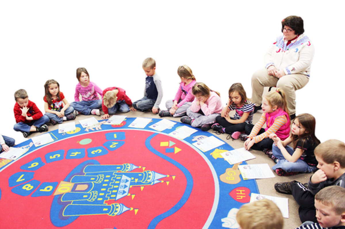 OVERSEEING: Kim Loomis (right) volunteers in the kindergarten classroom at LeRoy Elementary. Loomis is one of nearly 30 volunteers who help at the district's elementary schools.