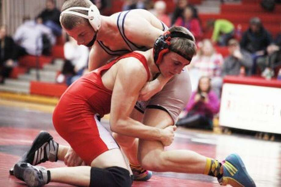 ALL OUT BATTLE: Big Rapids Jared Worden (top) looks to take down his opponent during Wednesday's wrestling action. Worden went 2-0 for the Cardinals, who set the school record for dual wins in a season. (Pioneer photo/Martin Slagter)