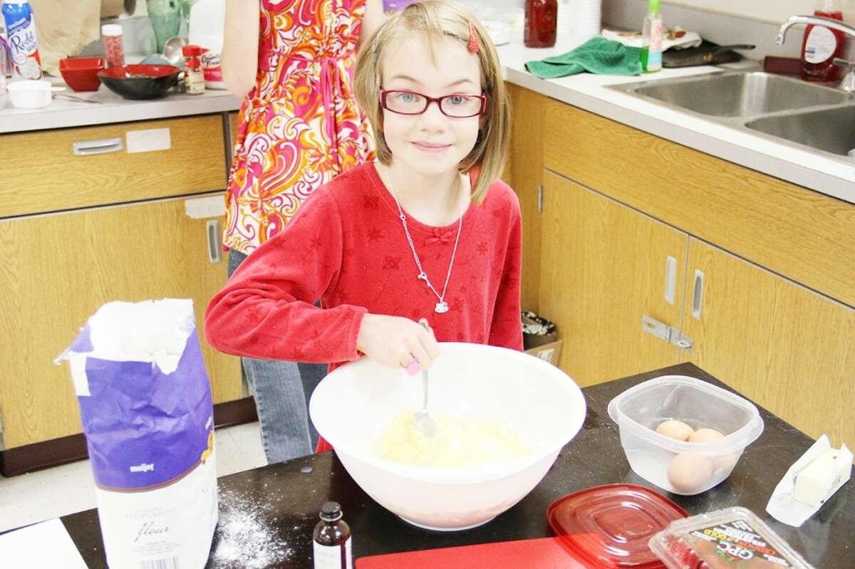 STIRRING: Megan Ebels, 7, stirs ingredients together to make German puff pancakes. Megan won the junior prize at the competition. (Herald Review photos/Sarah Neubecker)