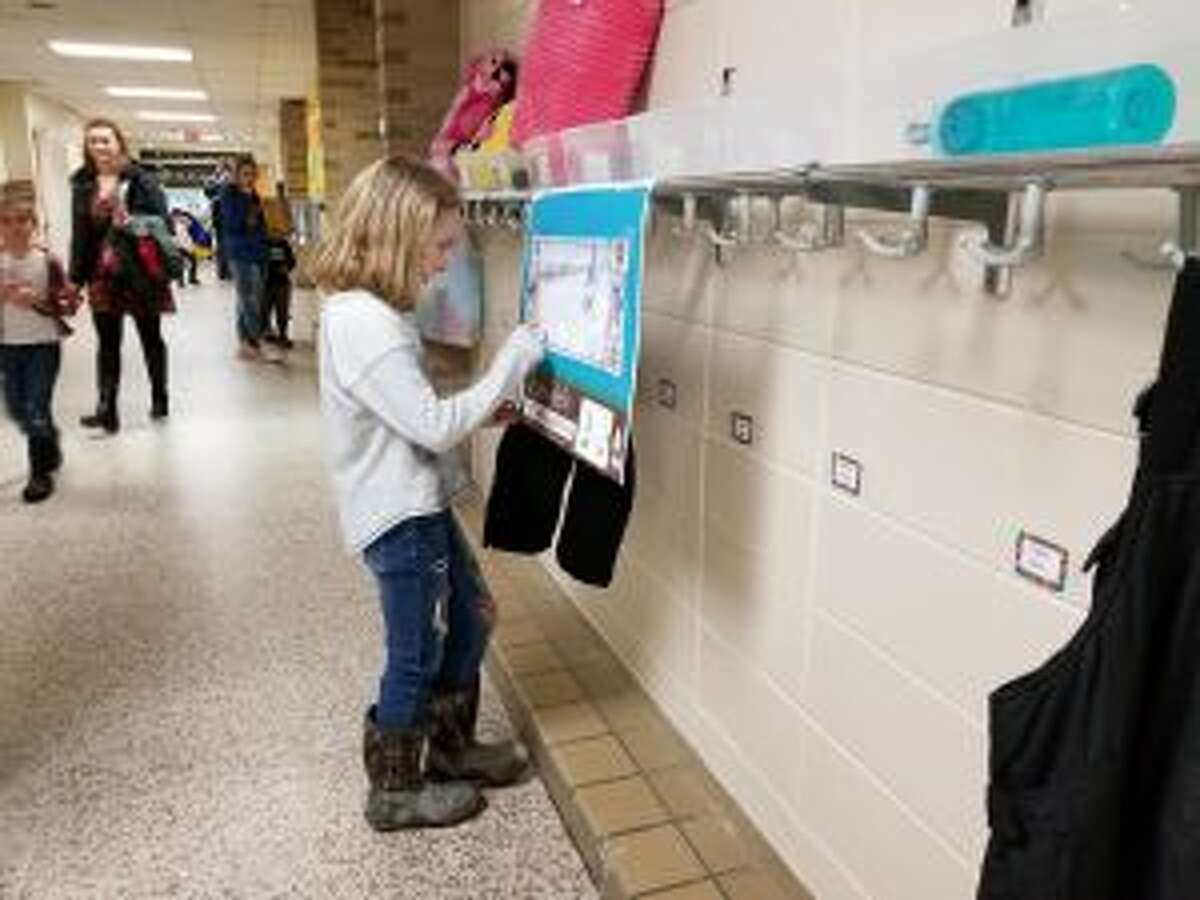 """A portion of the family night included a book walk, during which students, such as (pictured) Danika Clark, would follow a trail through the halls while reading the story """"The Mitten"""" by Jan Brett."""