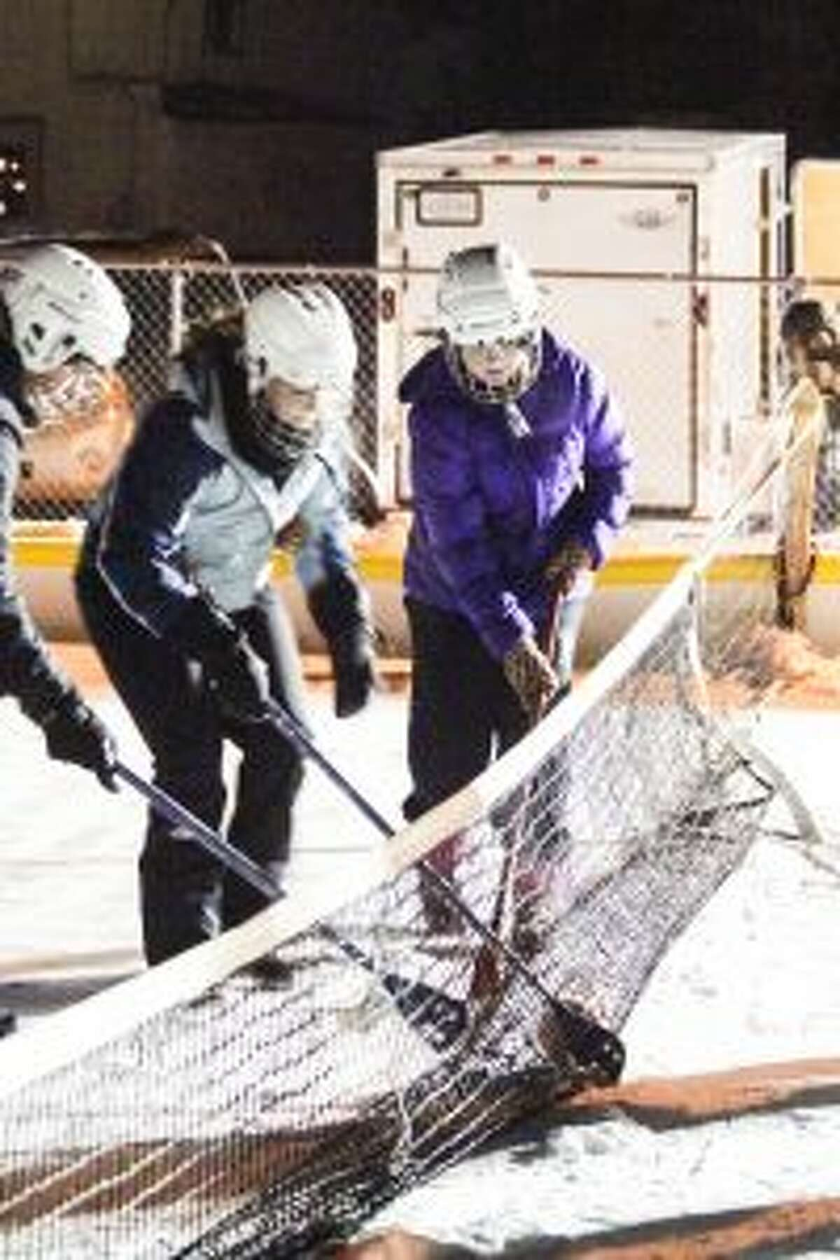 """GET THE BALL: Broomball players battle for the ball during Thursday night's tournament at the ice rink in Evart. The tournament kicked off the """"I Heart Evart"""" customer appreciation event from 15 members of the Evart Downtown Development Authority."""