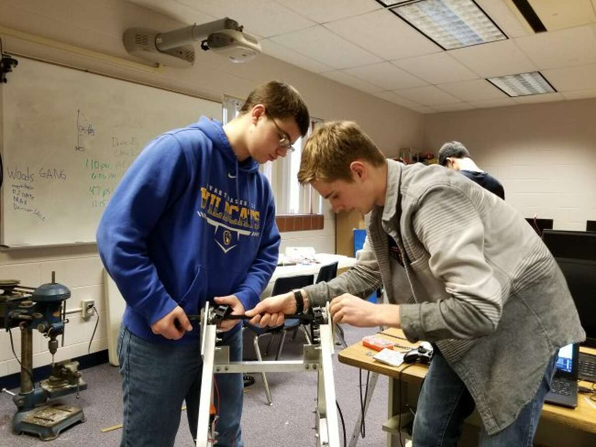 """Evart High School students (from left) Scott Whitman and Nathan Woods work on their robot in one of the final days before """"bag day,"""" when the robot has to be bagged and cannot be worked on again until their first competition of the season. (Herald Review photos/Meghan Gunther-Haas)"""