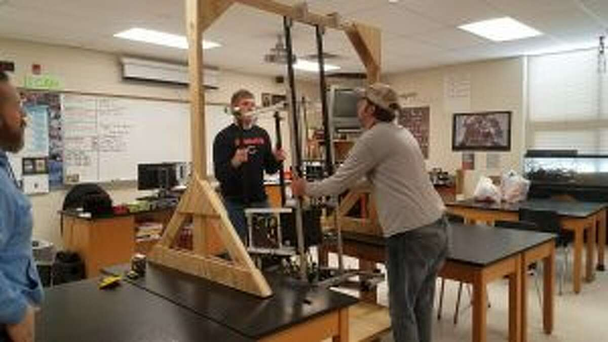 Reed City High School team members and their coach, Brad Smith, test their robot to make sure it can complete one of the final portions of the competition challenge, during which each of the robots is tasked with climbing.