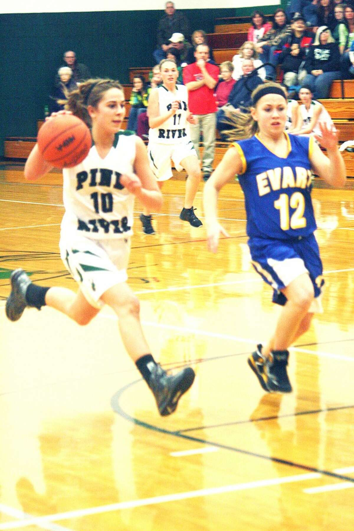 Two for Two: Kassy Nelson (10) drives past Evart's Tabby Turley (12). (Herald Review photo/John Raffel)