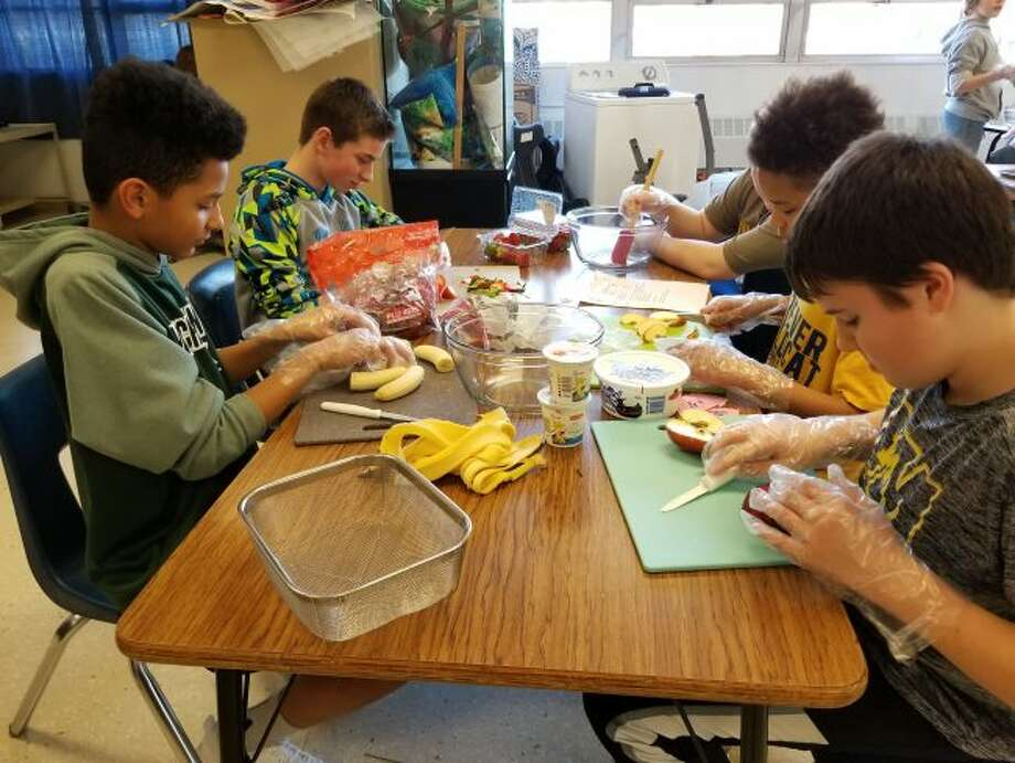 Evart Middle School students cut the different fruits needed for their recipe during Wildcat FUNatics on Tuesday, Feb. 27. The program teaches students how to create nutritional snacks, as well as how to have fun while staying active. (Herald Review photo/Meghan Gunther-Haas)