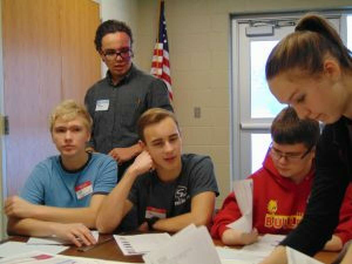 Members of the Chippewa Hills School District robotics team read through the instructions of the 2013 FIRST challenge guidelines during the networking event on Wednesday.
