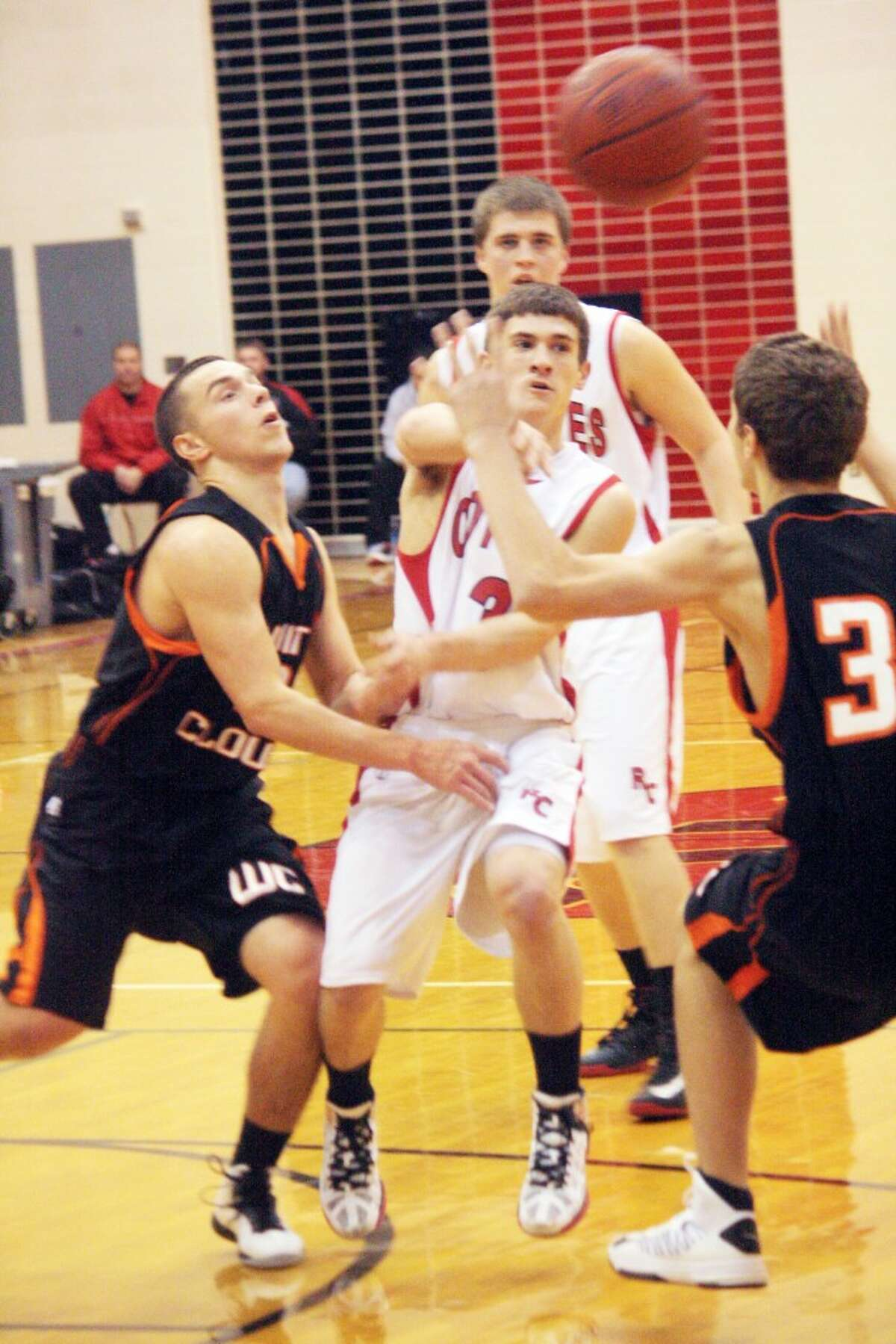 DRAWING ATTENTION: Reed City guard Joshua Saez (middle) makes a pass through traffic during Monday's game against White Cloud. The Coyotes defeated White Cloud 73-37 to improve to 6-4 on the season. (Herald Review photo/John Raffel)