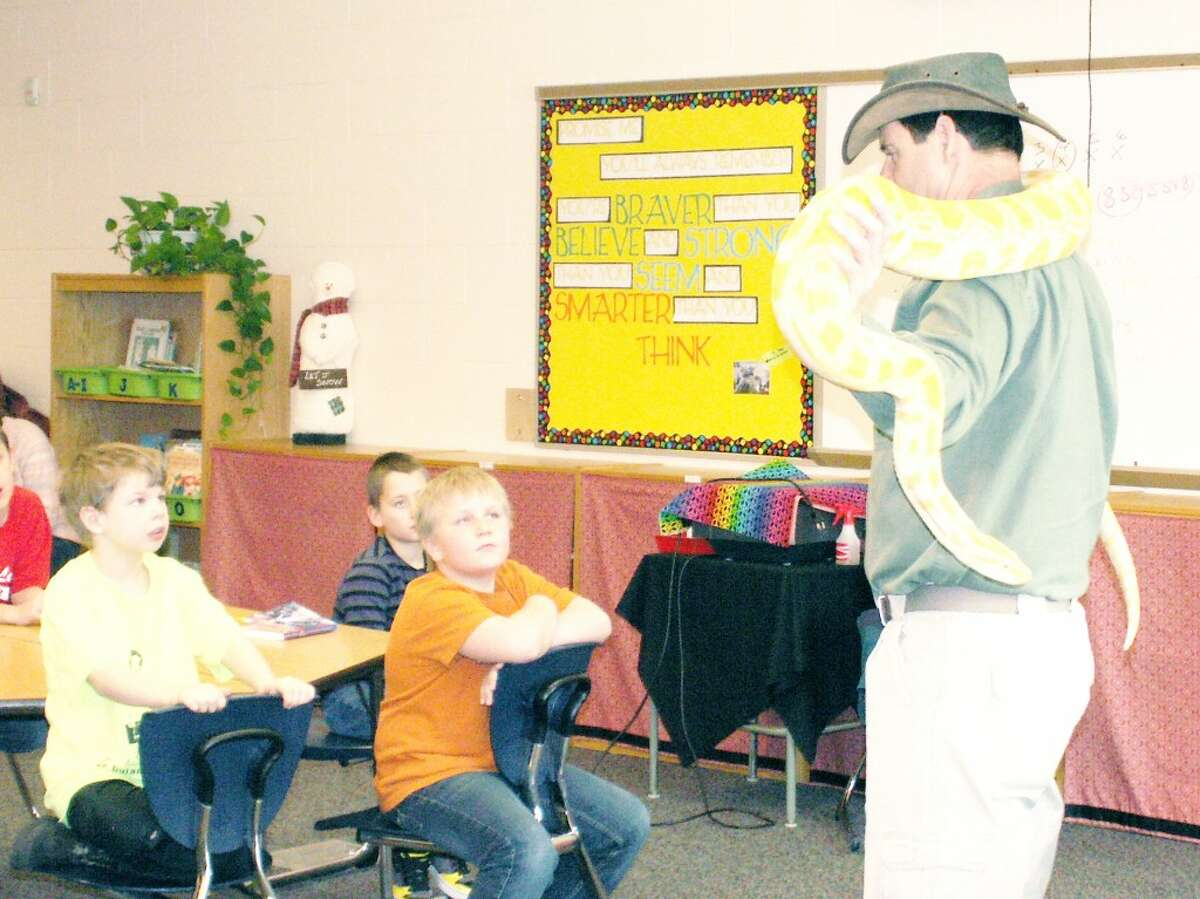 """MEETING NEW FIRNEDS: Reed City student Logan Ringler, right, curiously watches Edna, a 9ft Albino Burmese Python , while his classmate, Jeremiah Ireland, left, is a little unsure about being that close. Jeremiah says, """"I really don't like any snakes."""" (Herald Review photo)"""