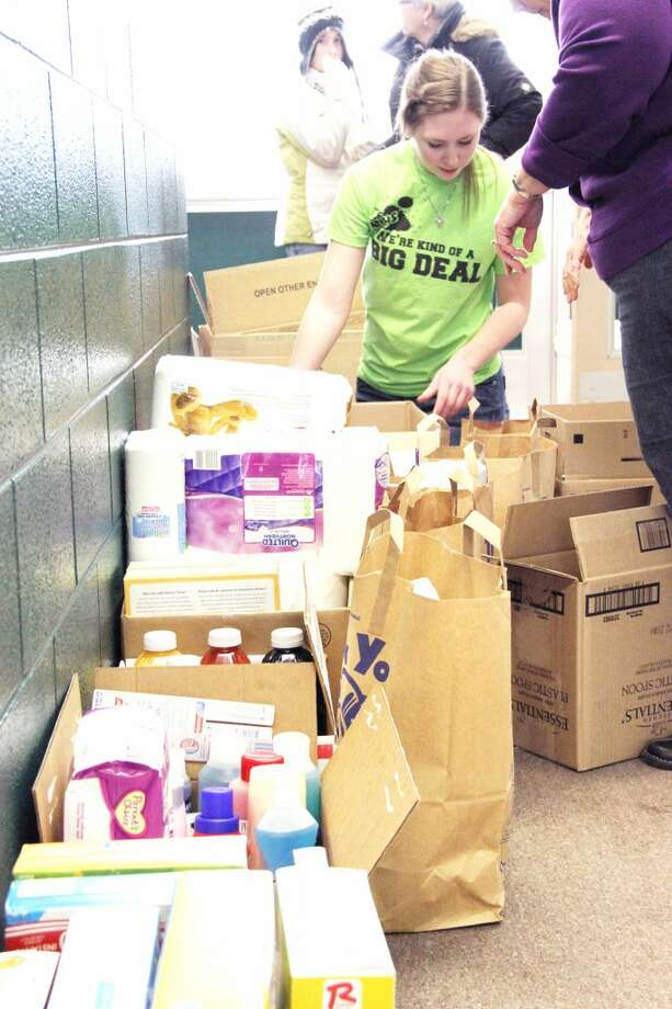 HELPING OUT: Pine River High School junior Olivia Storch stacks nonperishable food items collected at Tustin Elementary School on Monday. The district held various service events during the day to honor Martin Luther King Jr. Day. (Herald Review/Sarah Neubecker)