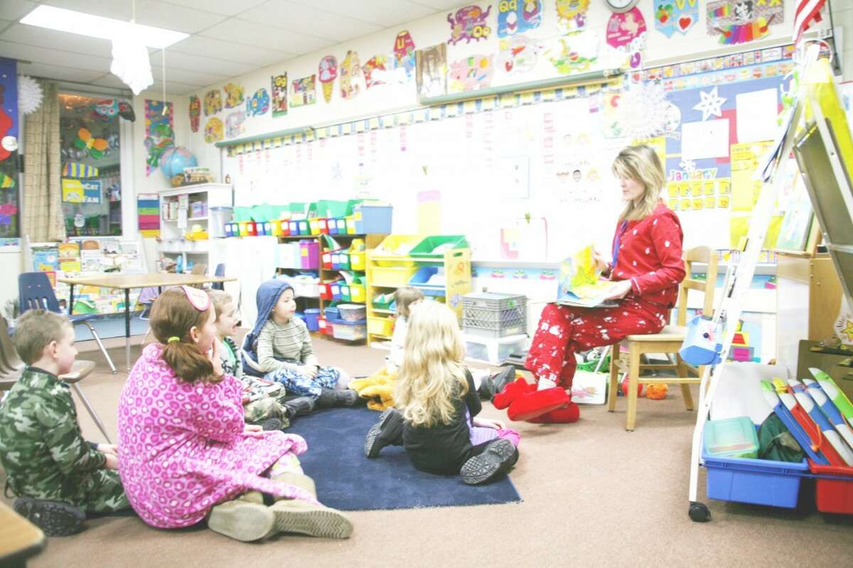 """BEDTIME STORIES: First-grade teacher Sarah Ladd hosts story time in her classroom. Attendees at Thursday's Family Night were encouraged to wear pajamas for """"bedtime stories."""" Several classrooms were open for story time. (Herald Review photos/Lauren Fitch)"""