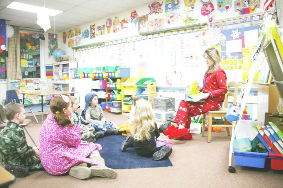 "BEDTIME STORIES: First-grade teacher Sarah Ladd hosts story time in her classroom. Attendees at Thursday's Family Night were encouraged to wear pajamas for ""bedtime stories."" Several classrooms were open for story time. (Herald Review photos/Lauren Fitch)"