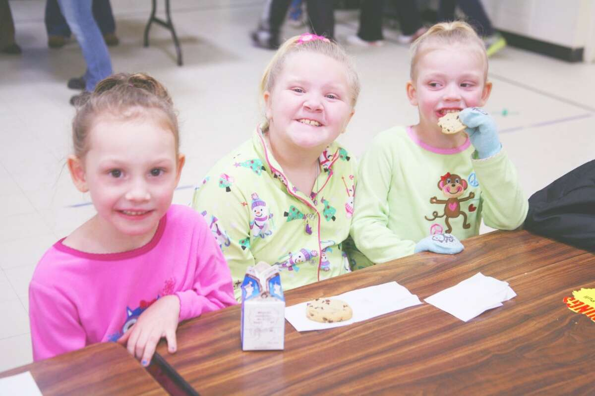 FAMILY NIGHT: (From left to right) Paige Champagne, Rose German and Lauren Champagne enjoy milk and cookies at Evart's Family Night.