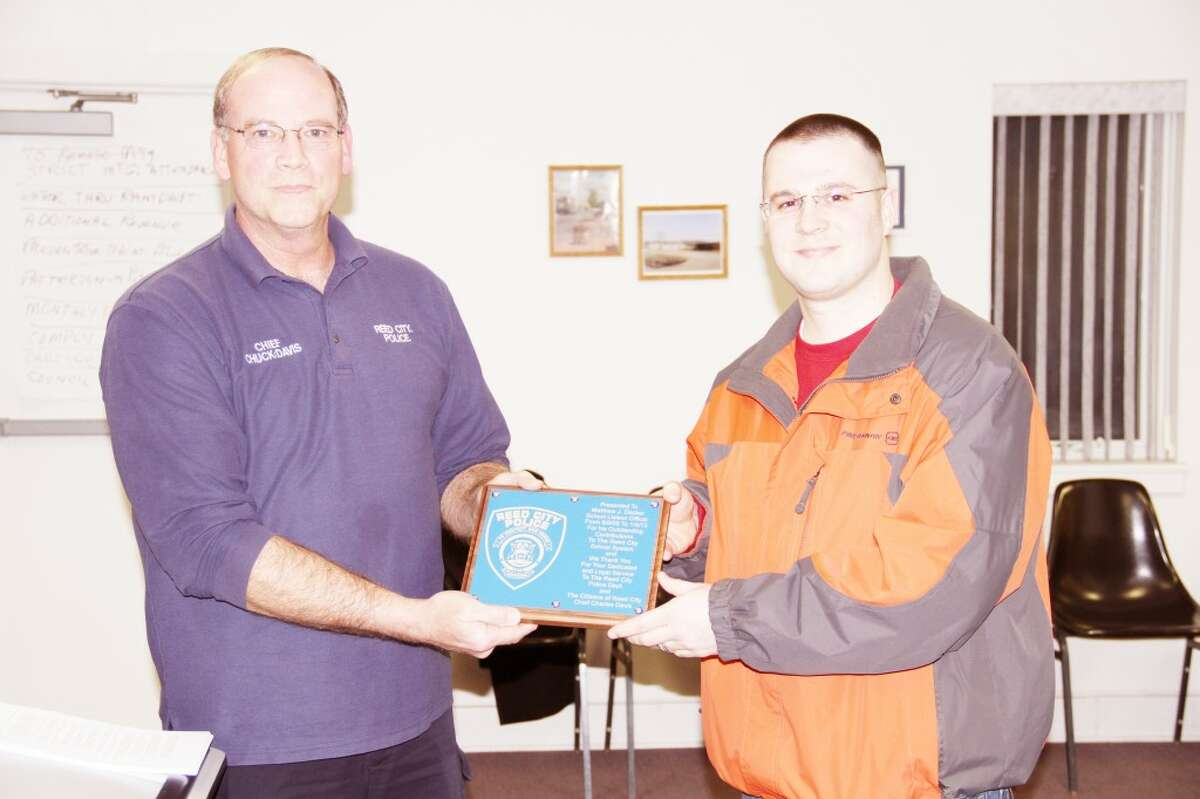 RECOGNIZED: Reed City Police Chief Chuck Davis (left) presents a plaque to Matt Decker, former Reed City Police Department schools liason officer who recently accepted a position at Ferris State University after three years with the Reed City Police Department. (Herald Review photo/Sarah Neubecker)