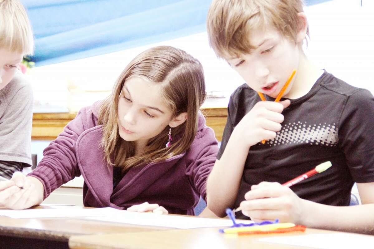 LEARNING: Evart Middle School fifth graders Laura Junker and Nolan Rohen write which traits are dominant and recessive based on long and short pipe cleaners during a Science Blast in the Class lesson on Jan.