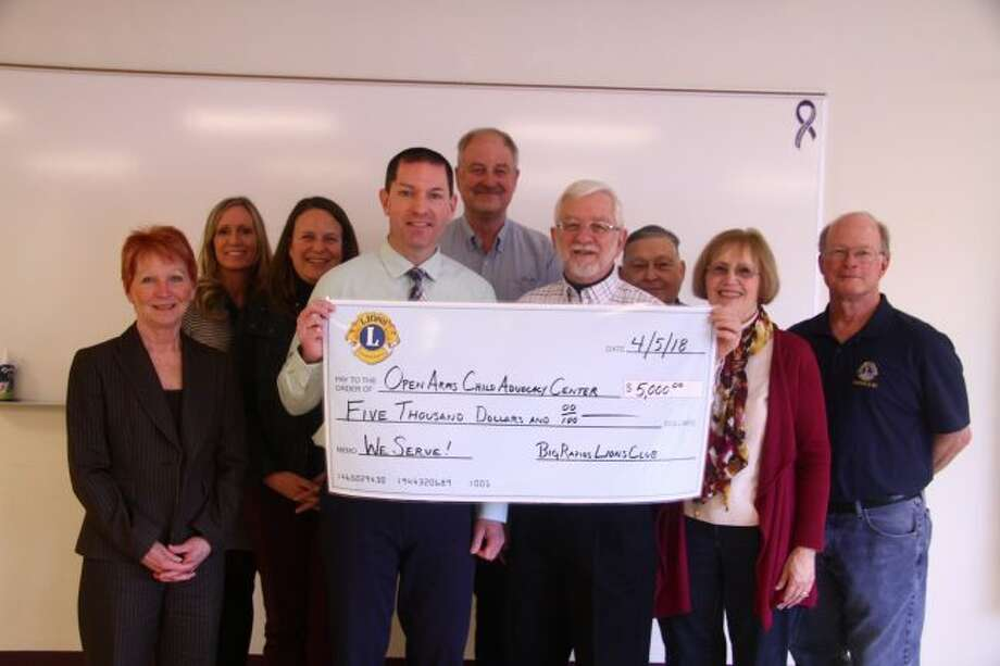Jim Eddinger (front left) receives a check donation from Big Rapids Lion Club President Tom Samuel (front right) for the Open Arms Child Advocacy Center, surrounded by Lions Club members and members of the child advocacy development team. (Pioneer photo/Emily Grove)