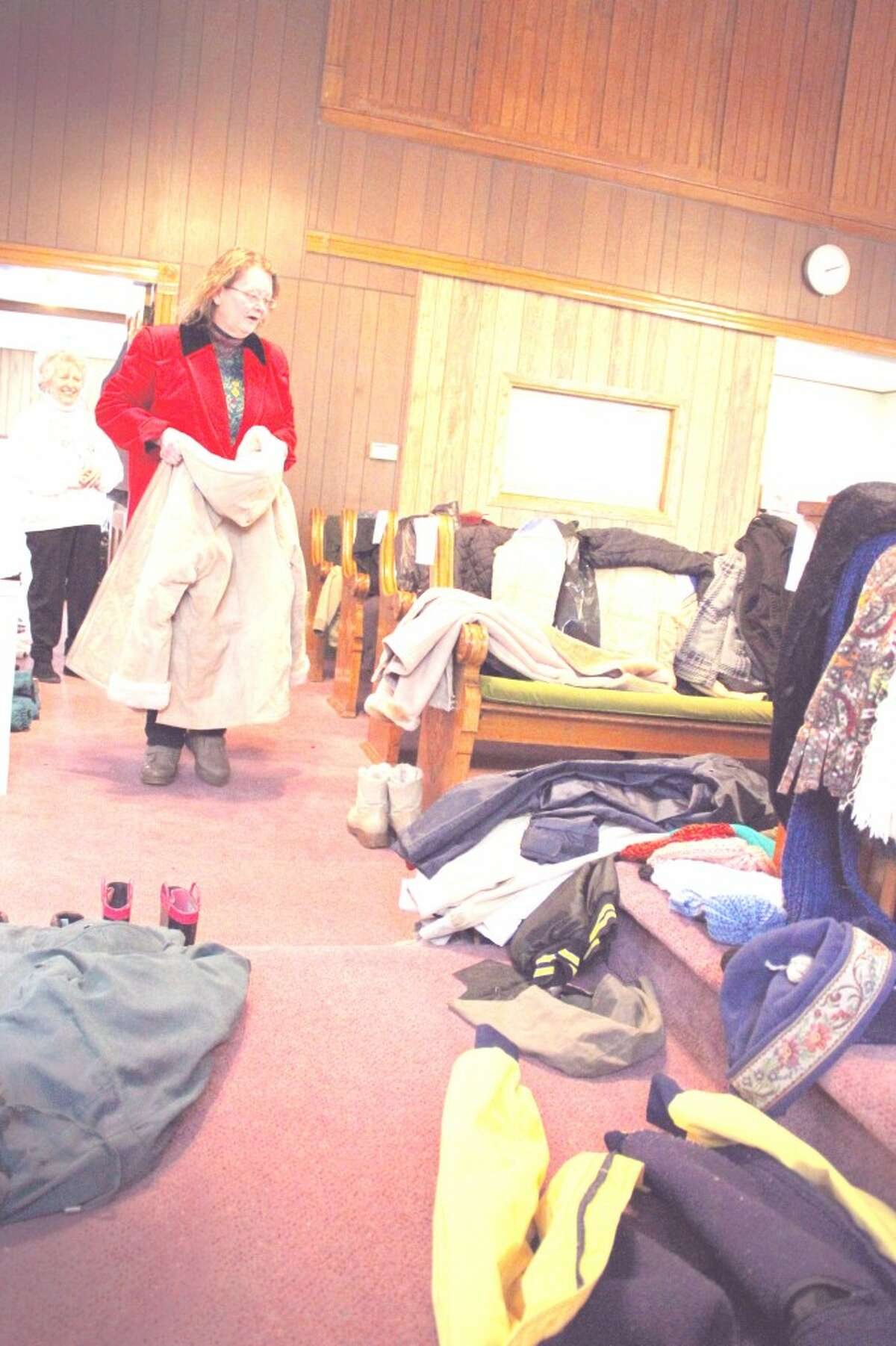 FREE COATS: Ivy LuuKkonen looks at some coats at the former Seventh Day Aventist Church in Reed City. The Reed City Area Ministerial Association gives away free winter coats, hats and mittens to those in need from 2 to 4 p.m. every Tuesday. (Herald Review photo/Sarah Neubecker)