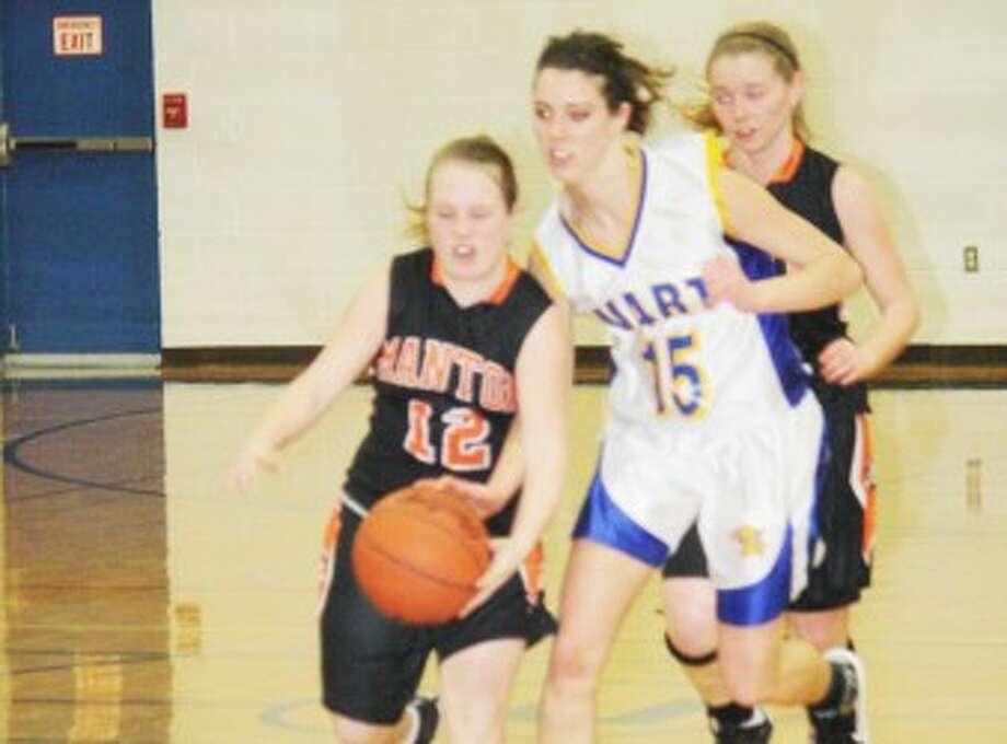 PRESSURE: Evart's Mara VanOrder (15) looks to steal the ball from a Manton player during Thursday's high school basketball action at Evart High School. (Pioneer photo/John Raffel)