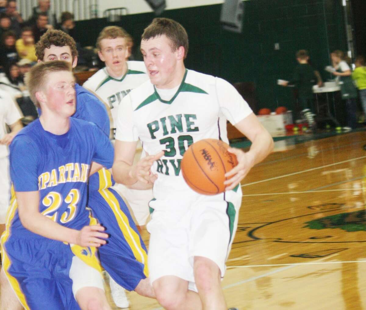 IN THE LANE: Pine River's Devin Ruppert (right) drives to the basket against Mason County Central on Monday. (Herald Review photo/John Raffel)