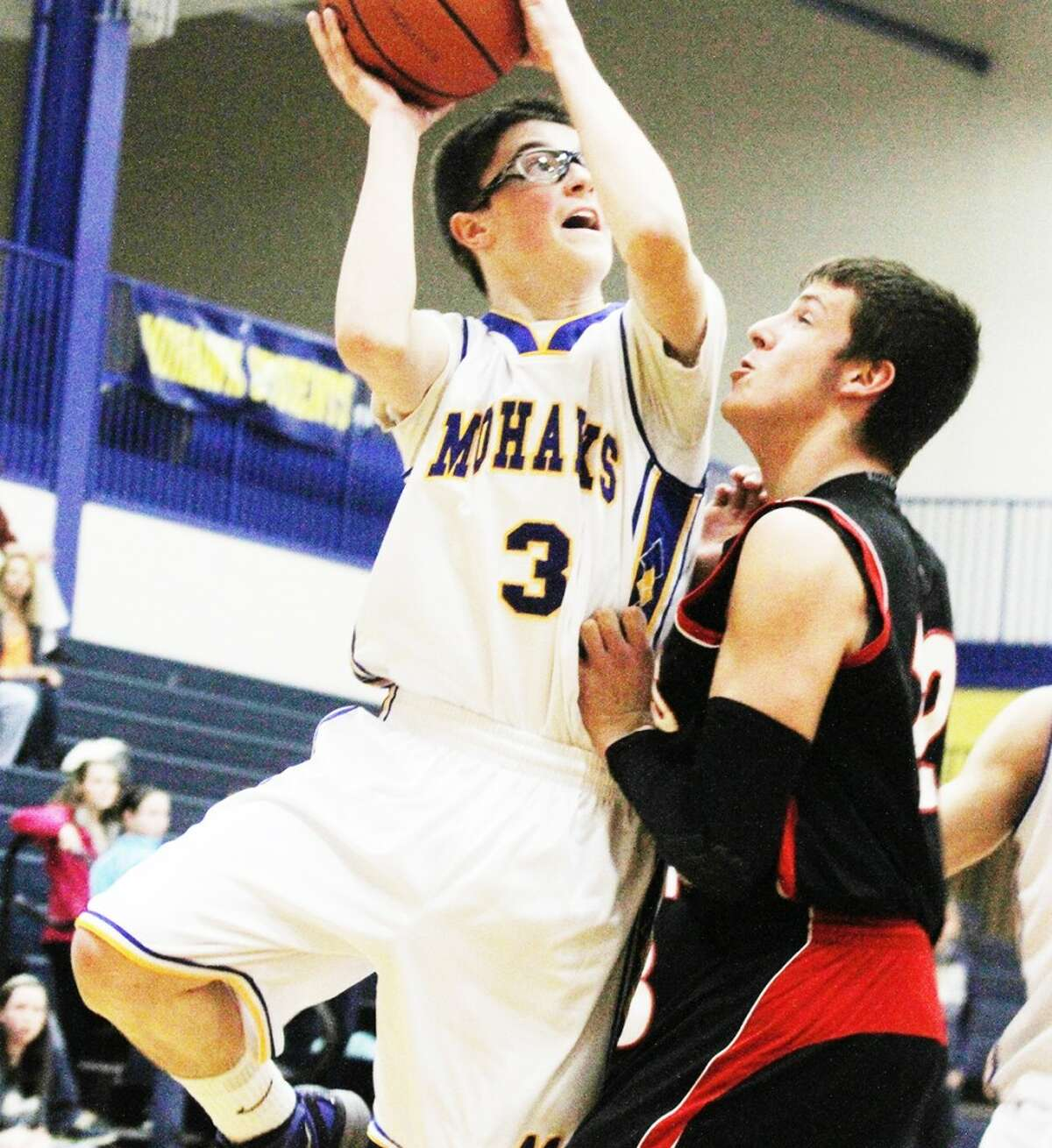 ROUGH GAME: Morley Stanwood's Tim Cairndruff (left) drives to the basket while being defended by Kyle Wright of Reed City. (Herald Review photo/Bob Allan)