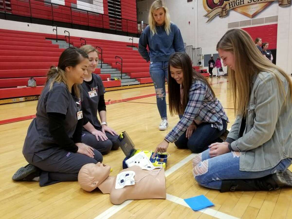 Ferris State University students Nadia Estrada (front) and Savanah Deshano walk Reed City high-school (from left) Hana Andrus, Alyssa Olds and Sidni Rushford through the process of using an AED as part of a CPR lesson on Monday, April 9. (Herald Review photos/Meghan Gunther-Haas)