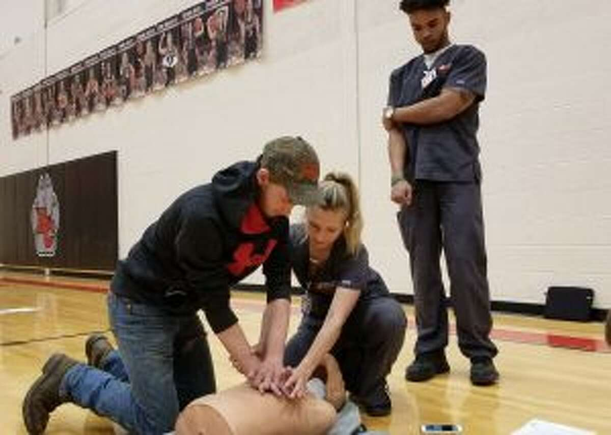 Ferris students Hakeem Dodd (standing) and Lauren Doyle instruct Reed City high-schooler Chandler Larson in the technique used to administer CPR.