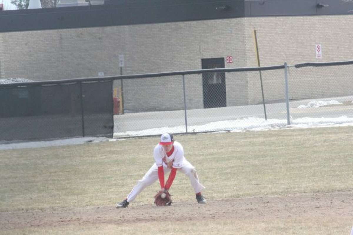 Brandon Wirth scoops up a ground ball against Evart;