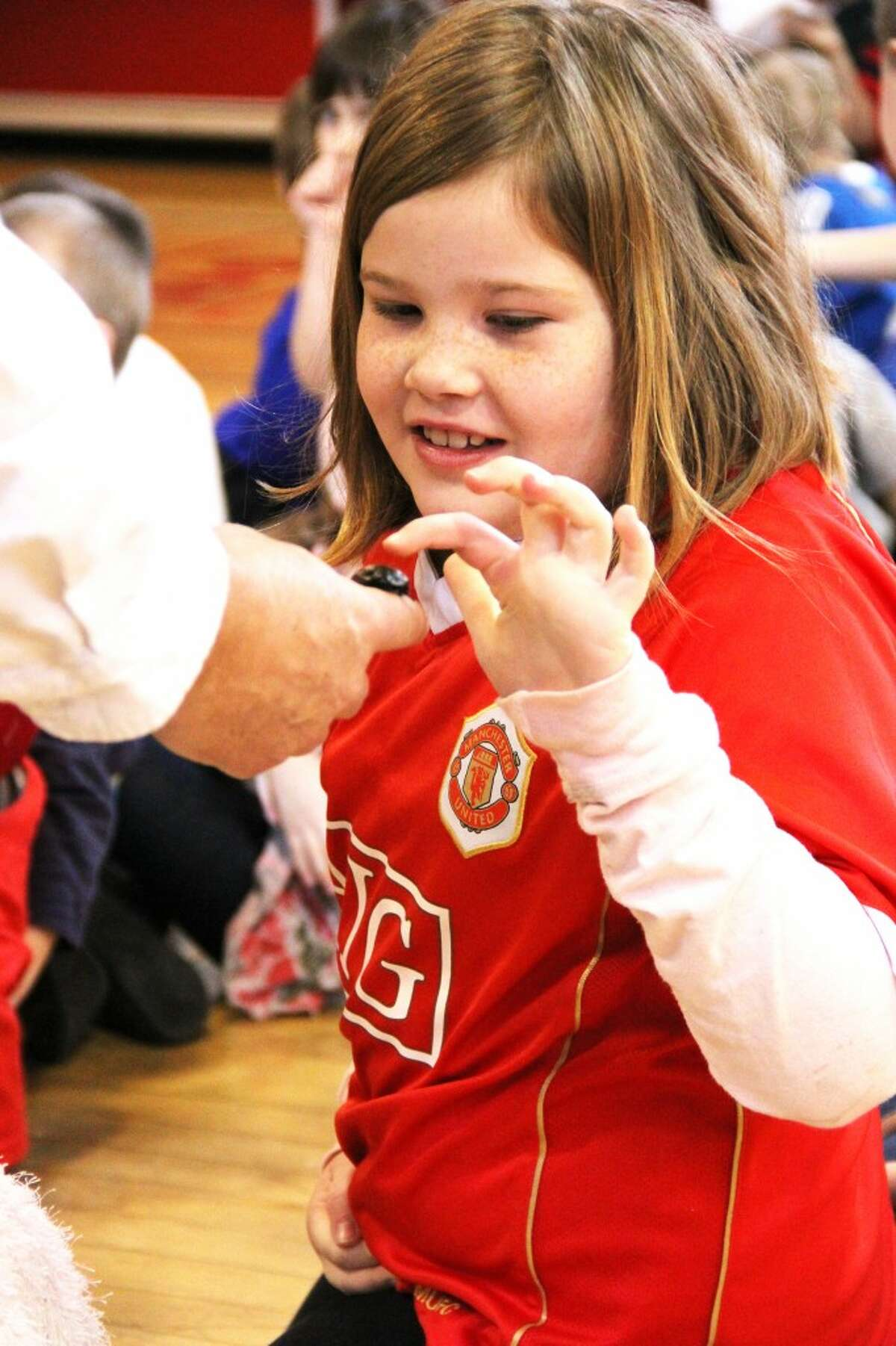 A Trinity Lutheran School student touches the outer shell of a cockroach from Madagascar at a school assembly on Friday. (Herald Review photo/Sarah Neubecker)