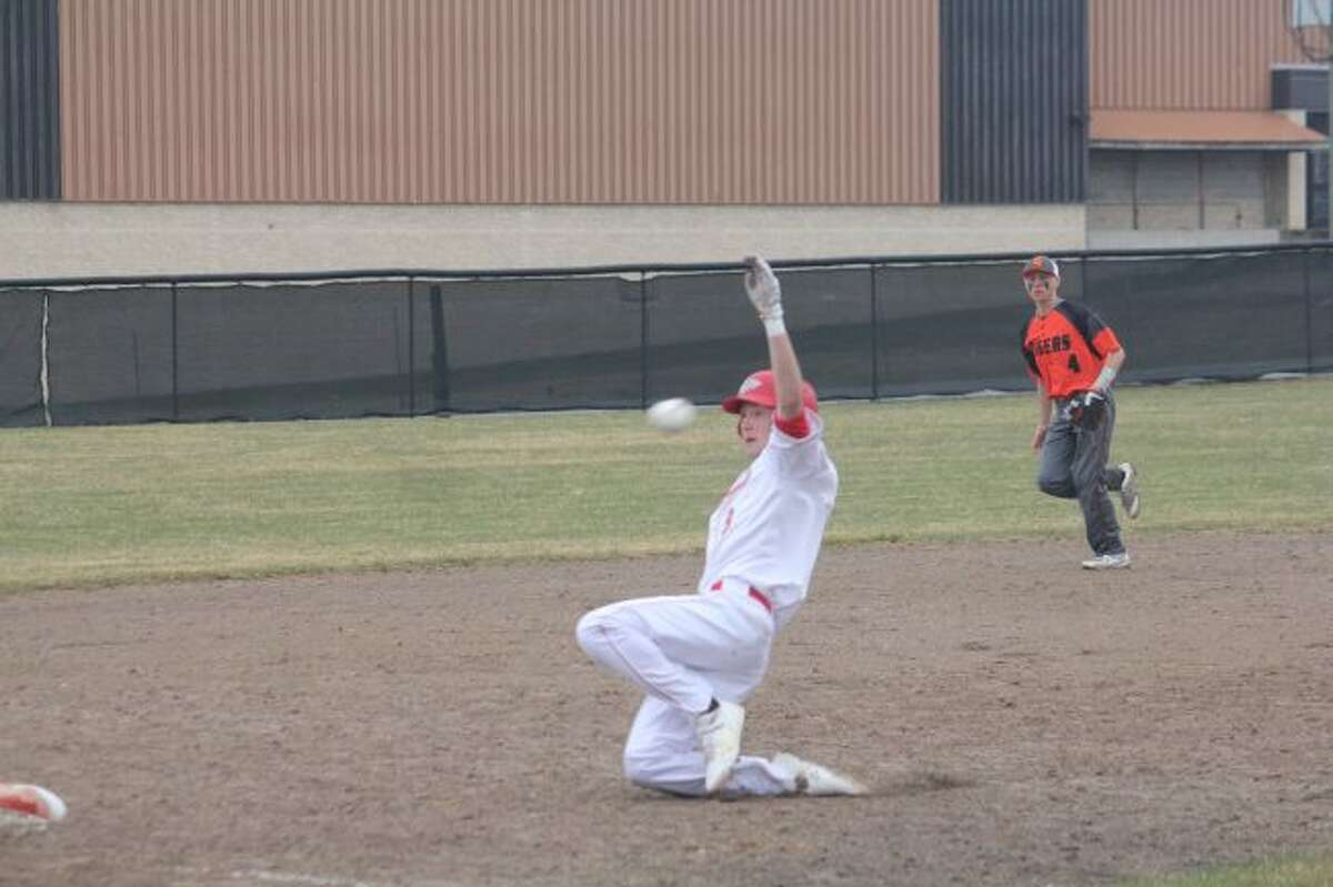 Cody Kailng slides ahead of the throw into third base.