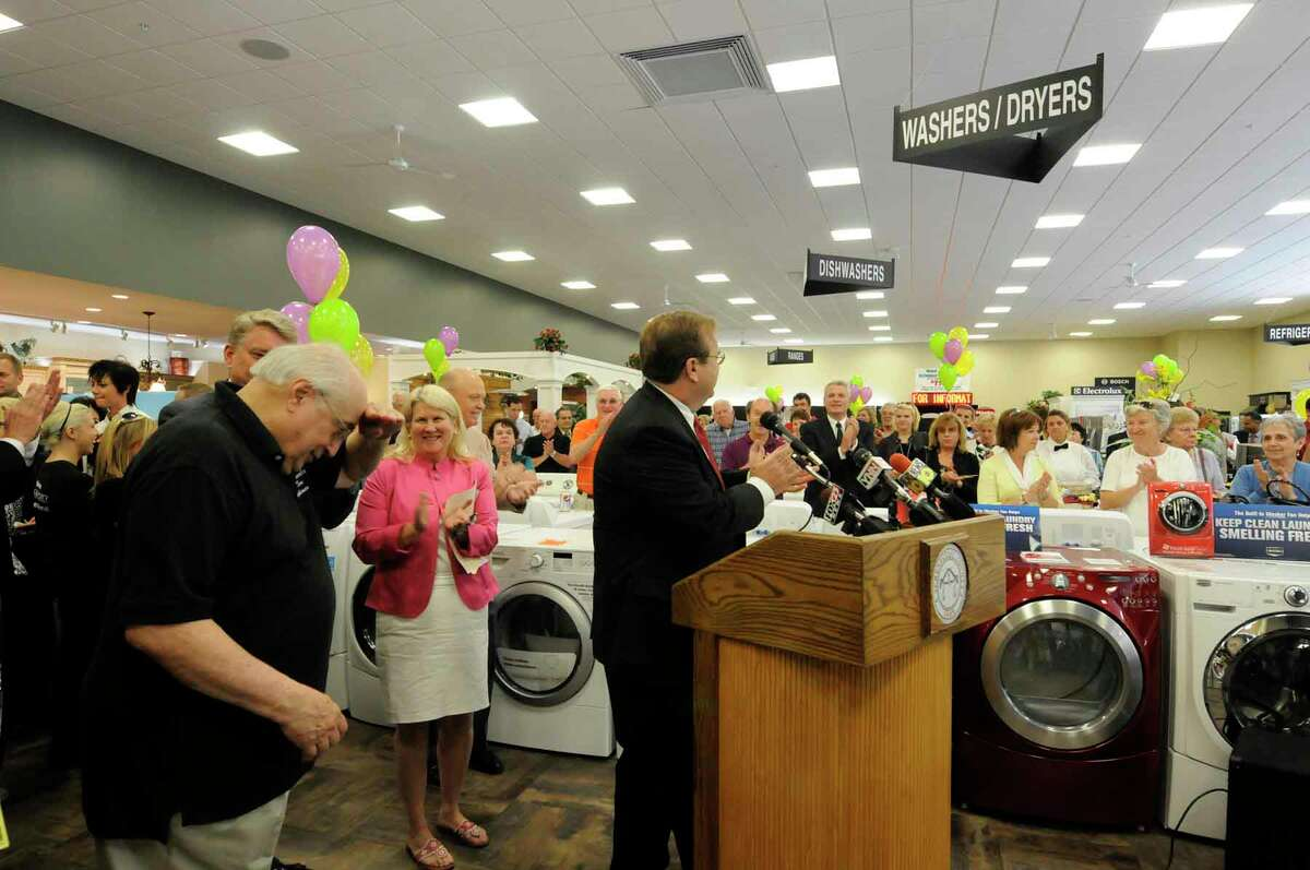 John Marcella,left, takes a bow during the grand opening of the new and expanded John D. Marcella and Sons Appliances on Broadway in Schenectady, New York 5/20/2010.( Michael P. Farrell / Times Union )