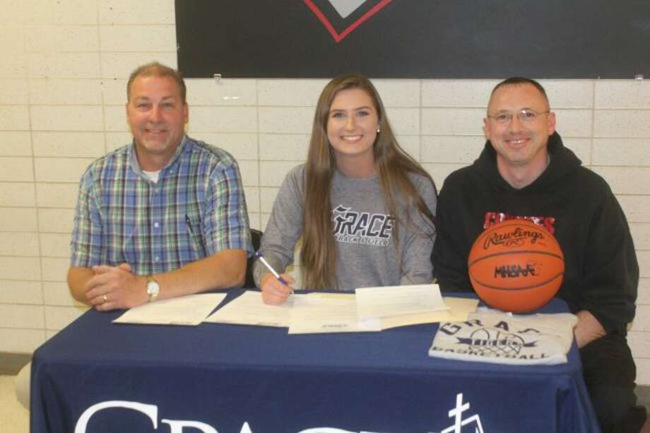 Emily Libey (center) signs with Grace Bible College. At left is Reed City coach Brian Koopman. At right is assistant Brian Hammond.