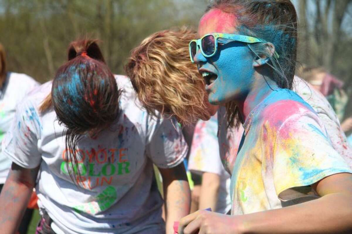 Rylee Harrison laughs after being covered with dye packets during Saturday's Coyote Color Run.