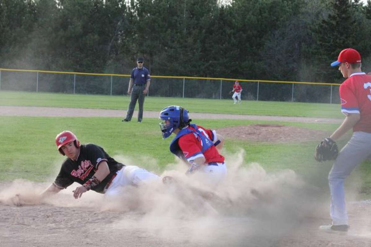 Stephen Showan slides safely into home plate against Chippewa Hills.