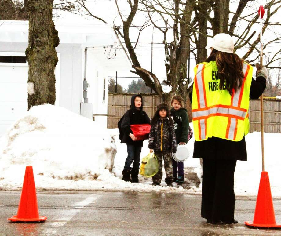 GUARD: Kelly Elder sets out cones and holds a stop sign on Cedar Street to end her shift as a crossing guard for Evart Elementary School on Thursday. The program began late last year as part of the Evart Community Watch program. (Herald Review/Sarah Neubecker photo)
